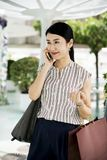 Woman Holding Smartphone and Paper Bag royalty free stock images