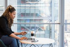 Woman Holding Smartphone Sitting in Front of Laptop on Table stock images