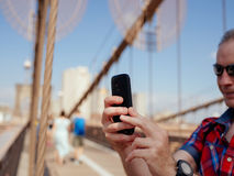 Woman Holding Smartphone Standing on Bridge Stock Photography