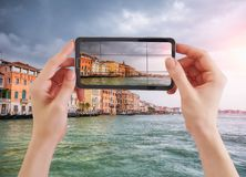 Woman taking photo of Canal Grande and venetian cityscape, Venice, Italy. Woman holding smartphone taking photo of Canal Grande and venetian cityscape, Venice Stock Photos