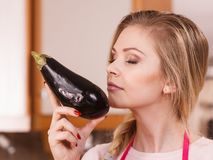 Woman holding and smelling eggplant. Woman in holding and smelling delicious eggplant vegetable. Healthy lifestyle, eating veggies, superfood royalty free stock image