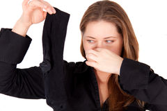 A woman is holding a smelly sock Royalty Free Stock Image