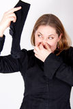 A woman is holding a smelly sock Royalty Free Stock Images