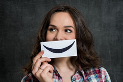 Woman Holding Smiley Emoticon. Young Woman Holding Smiley Emoticon Over Gray Background Royalty Free Stock Image