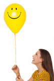 Woman holding smiley face balloon. Young woman holding smiley face balloon Stock Image