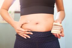 Woman holding snack food or dessert and squeeze her belly, Diet Stock Image