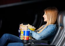 Woman Holding Snacks While Watching Movie At Stock Photo