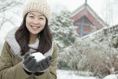 Woman Holding snowball outside in park Royalty Free Stock Image