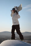 Woman holding snowboard. Close up of woman on top of hill wearing sky goggles and holding snowboard, winter sports scene stock image