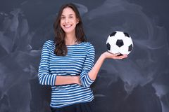 Woman holding a soccer ball in front of chalk drawing board Stock Photo