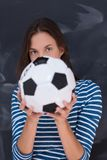 Woman holding a soccer ball in front of chalk drawing board Stock Image
