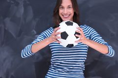 Woman holding a soccer ball in front of chalk drawing board Stock Photos