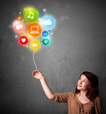Woman holding social media balloon. Pretty young woman holding colorful social media icons balloon Royalty Free Stock Photography