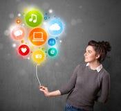 Woman holding social media balloon. Pretty young woman holding colorful social media icons balloon Stock Photo