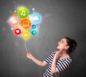 Woman holding social media balloon. Pretty young woman holding colorful social media icons balloon Royalty Free Stock Images