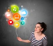Woman holding social media balloon. Pretty young woman holding colorful social media icons balloon Stock Images