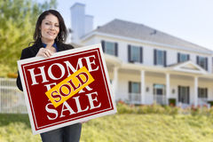 Woman Holding Sold Home Sale Sign in Front of House. Smiling Hispanic Woman Holding Sold Home For Sale Sign In Front of Beautiful House Stock Image