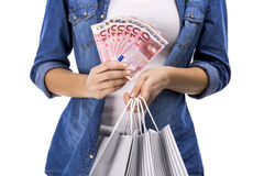 Woman holding some Euro currency notes. Beauitful woman holding shopping bags and some Euro currency notes,  over white background Royalty Free Stock Photography