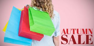Composite image of woman holding some shopping bags. Woman holding some shopping bags against pink background royalty free stock images