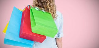 Composite image of woman holding some shopping bags. Woman holding some shopping bags against pink background royalty free stock image