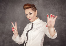 Woman holding something in her hand. On the blackboard background Stock Photo