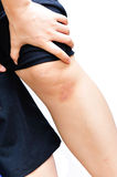 Woman holding sore leg Royalty Free Stock Image