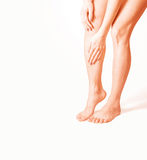 Woman holding sore leg, on a white background Royalty Free Stock Photos