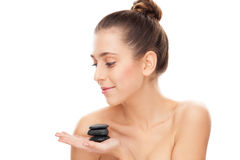 Woman holding spa stones. Young woman over white background Royalty Free Stock Photo