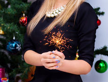 Woman holding sparkler in her hand Stock Photo