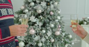 Woman holding sparkling champagne celebrating Christmas with her husband with xmas tree in the background.