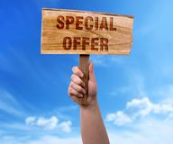 Special offer wooden sign. A woman holding special offer wooden sign on blue sky background Stock Photography