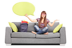 Woman holding a speech bubble seated on a sofa Royalty Free Stock Photo