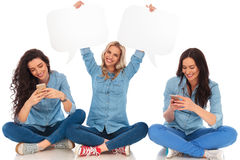 Woman holding speech bubbles near friends texting on phones. Woman holding speech bubbles near friends texting on their phones on white background Stock Photography
