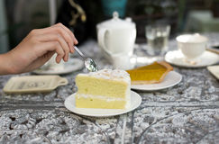 Woman holding spoon eating coconut cake with cup of tea on vintage metal table stock photos