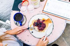 Woman Holding Spoon and Fork With Blackberries on Plate Beside Blue Ceramic Mug on White Wooden Table stock photography