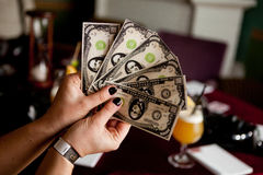 Woman holding a spread of fake money. Woman displaying a Spread of fake Cash in bar Stock Images