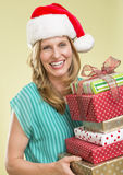 Woman Holding Stack Of Christmas Presents. Portrait of cheerful young woman holding stack of Christmas presents on colored background stock photos