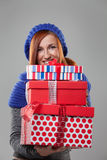Woman Holding Stack of Christmas Presents. Smiling Woman with Red Hair Holding Stack of Christmas Presents in Studio royalty free stock photos