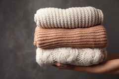 Woman holding stack of folded warm knitted sweaters. Against dark background stock image