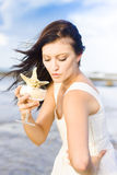 Woman Holding Star Fish Cocktail. Young Beautiful Woman Sipping From A Cocktail Glass Containing A Marine Star Fish In A Party And Vacation Concept Royalty Free Stock Images