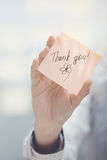 Thank you text on adhesive note. Woman holding sticky note with Thank you text Stock Photos