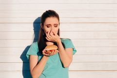 Woman Holding a Stinky and Disgusting Burger. Girl covering her nose because of Bad smelling dangerous food royalty free stock photos