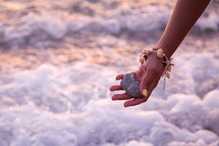 Woman holding stone near sea. At sunset Royalty Free Stock Image