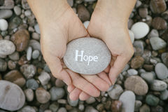 Woman holding stone with the word Hope in her palms Royalty Free Stock Images