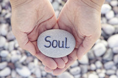 Woman holding stone with the word Soul in her palms. Soul. Woman holding stone with the word Soul in her palms. Close up stock image