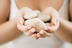 Woman holding stones for hot stone therapy Royalty Free Stock Photo