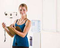 Woman holding stopwatch and clipboard royalty free stock images