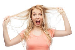 Woman holding strand of her hair. Hair care, hairstyle and people concept - young woman or teenage girl holding strand of her hair stock photos