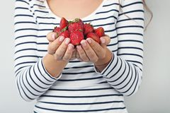 Woman holding strawberries. Young woman holding strawberries in hands on grey background Stock Photo