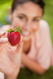 Woman holding a strawberry at arms reach Stock Photo